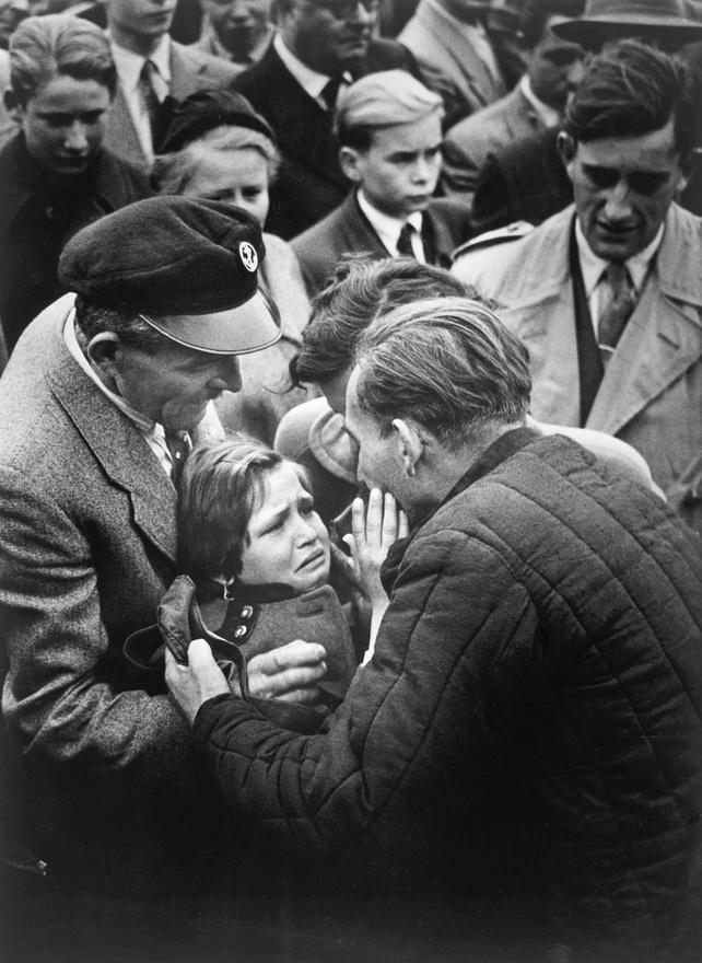 1956. Egy hazatérő német hadifogoly viszontlátja a lányát.A kislány egyéves kora óta nem látta az apját.A képen látható férfi volt az egyik utolsó hadifogoly, akit a Szovjetunióból szabadon engedtek a második világháború után.1956-ban a magyarországi politikai helyzet heves vitát váltott ki a Holland Sajtófotósok Szövetségében arról, hogy vajon le kell-e mondani a kiállítást szolidaritásból a magyar kollégák iránt, akik joggal aggódtak a sajtószabadságért a forradalom leverése után. Köztes megoldásként a kiállítást végül 1956 novemberéről 1957 márciusára halasztották.