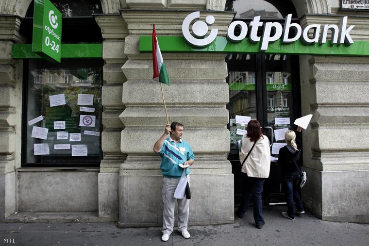 Demonstrálók feliratokat ragasztanak fel egy OTP-bankfiók ablakára 2013. augusztus 27-én a fővárosi Nagykörúton ahol devizahitelesek tüntettek a Nem adom a házam elnevezésű civil szervezet kezdeményezésére.