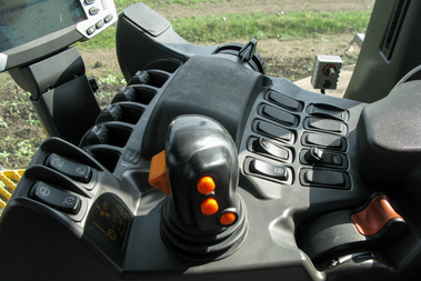 Joystick, mögötte kézi gáz, túloldalt a munkaeszköz állítókereke