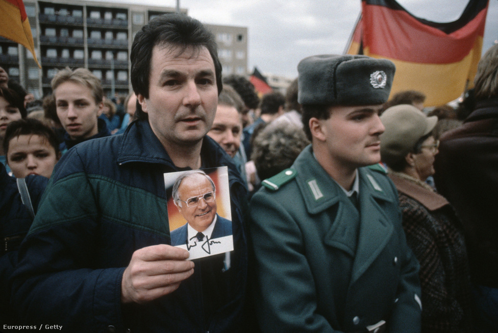 Helmuth Kohl kancellár képét tartja ez a két ország újraegyesítéséért tüntető férfi. Helmuth Kohl 1982-től volt az NSZK kancellárja. Az újraegyesítés folyamatának kidolgozása nagyrészt a kereszténydemokrata politikus nevéhez fűződik. Ő lett az egyesített Németország kancellárja is. 1998-as távozása után beárnyékolta a róla kialakult képet, hogy egy csúnya pártfinanszírozási botrányba keveredett: márkamilliókat szerzett pártja, a CDU számára.