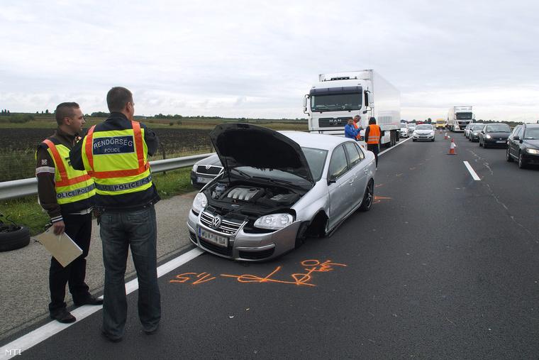 Összetört személyautók mellett helyszínelnek rendőrök az M5-ös autópályán Lajosmizse közelében 2015. szeptember 27-én ahol rendőrök elfogták azt a szerb férfit aki autójában 14 illegális bevándorlóval az igazoltatás elől menekülve balesetet okozott.
