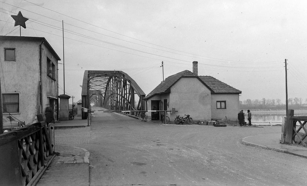 Az első világháború végéig Komárom egyetlen város volt, de a háború végén a település történelmi városrészét Csehszlovákiához csatolták, és Komárnónak nevezték el. A fotó 1960-ban készült, és bár konkrétan ezen a fotón nincs tömeg, mégis ebben az évben indult meg a tömeges turizmus, mert ekkor törölték el a vízumkényszert a Csehszlovákiába utazók számára. Így ettől az évtől Komárom a magyar-csehszlovák határ legforgalmasabb határátkelőjévé vált, ahogy azt Stefano Bottoni a Komárom/Komárno ikerváros államszocialista szociológiáját kutató tanulmányában is írja. A Magyarország felőli határátlépések száma 1960 folyamán meghaladta a 150 ezret, 1962-ben pedig elérte a 200 ezret. Csehszlovákiából 1960-ban 77 ezer, 1962-ben már 128 ezer belépést regisztráltak. A határátlépés a képen látható dunai összekötő hídon keresztül zajlott.