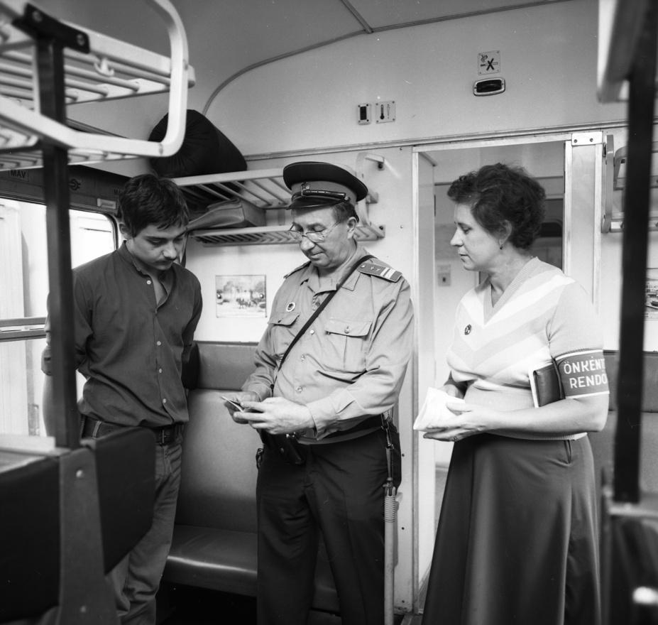 """""""Az önkéntes rendőr ahol tud, segít, ahol nem akarják, ott is"""" - szólt a dallamos szólásmondás a Kádár-korban. A fotón látható önkéntes rendőr éppen az útlevélellenőrzésnél néz fontoskodva egy hazai vonaton. 1975-ben 6 ezer, 1986-ra 11 ezer önkéntes rendőr tevékenykedett Magyarországon, akik a saját lakókörnyezetükben folyamatosan részt vettek rendőrrel, határőrrel közös járőrszolgálatban, írja Forró János a Kádár-rendszer rendvédelmi szervezeteiről szóló tanulmányában."""