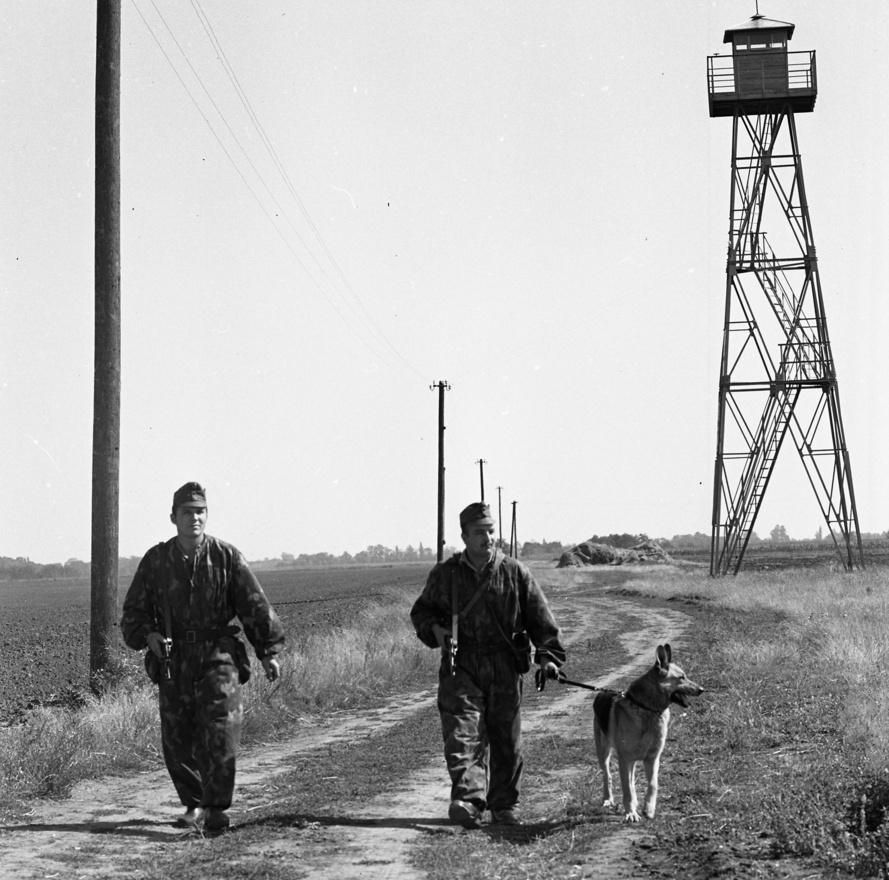 """1977-ben kutyás határőrök járőröznek a magyar-jugoszláv határon. Bár nem lehetett pontosan behatárolni, hogy a fotó melyik határszakaszon történt, de lehet, hogy éppen ott, ahol a napokban készül el a magyar-horvát határzár, amit az Ázsiából érkező migránstömeg megfékezésére húzott fel a magyar kormány. Akkoriban elegendő volt a magasles, aki illegálisan akart átlépni, az inkább kifelé ment, nem befelé jött és a disszidensek – ha tehették – a nyugati határon szöktek. A Magyarország a XX. században című könyv azt írja, hogy 1960-1980 között """"többen vándoroltak ki az országból, mint be az országba. 1988-ig évente 3–6 ezren vándoroltak ki és egy-kétezer fő vándorolt be. Az ország tehát nem kapcsolódhatott be az 1960–1970-es évek igen nagyarányú nemzetközi munkaerő-vándorlásába, melyet a fejlett tőkés országok gazdasági fellendülése hívott életre."""""""
