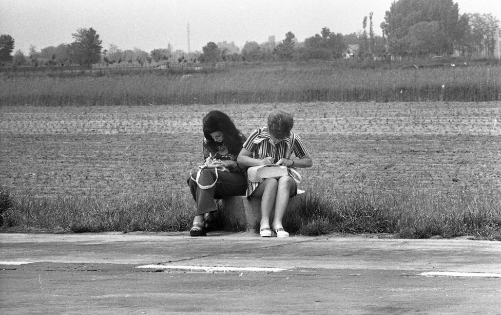 """Az 1978-ban Röszkén határátlépésre várakozó nők a tarló mellé kucorodva írják adataikat a határátlépéshez szükséges dokumentumokra. Viseletük a hetvenes évekbeli divatot tükrözi, a korábbi évekkel ellentétben eddigre már nem váltott ki heves reakciókat egy szupermini szoknya látványa. """"A miniszoknyához az igazán divatosan megjelenni akaró ifjú hölgyek tupírozott frizurát készíttettek maguknak"""" - fogalmaz Valuch Tibor, Kádár-korszakkal foglalkozó kutató, és hát tényleg. Az óriásfrizura határátlépés közben is tart."""
