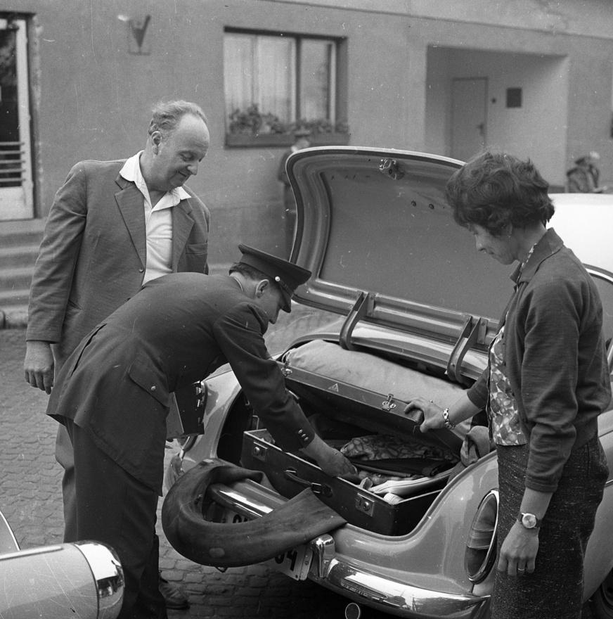 """A hatvanas évek közepén autóbuszjárat is indult Komárom és Komárnó között, ami a nyári hónapokban működött, írja a térséget kutató Stefano Bottoni, de a tehetősebbeknek a személyautós közlekedés is általánossá vált. Nemcsak a magyarok mentek örömmel, a csehszlovákok is érkeztek szép számmal a dunai határátkelőn. A fotó 1964-ben készült a csomagok átvizsgálása közben, az elegánsan kiöltözött utazó pár üdvözült mosolyából egyrészt arra következtethetünk, hogy nincs náluk semmi illegális (esetleg ügyesen elrejtették), illetve egybevág azzal, amit 1964. január 18-i számában írt a határátlépésekkel kapcsolatban a megyei Dolgozók Lapja: """"az utazási, illetve átlépési láz, legfrissebb értesülésünk szerint nem hagy alább. [...]. Az elmúlt évekhez képest háromszorosára emelkedett a Csehszlovákiából felől érkező külföldi vendégek száma is. A vadászszezon megindulásakor az Idegenforgalmi Hivatal több napon át rendkívüli, éjszakába nyúló szolgálatot tartott."""""""