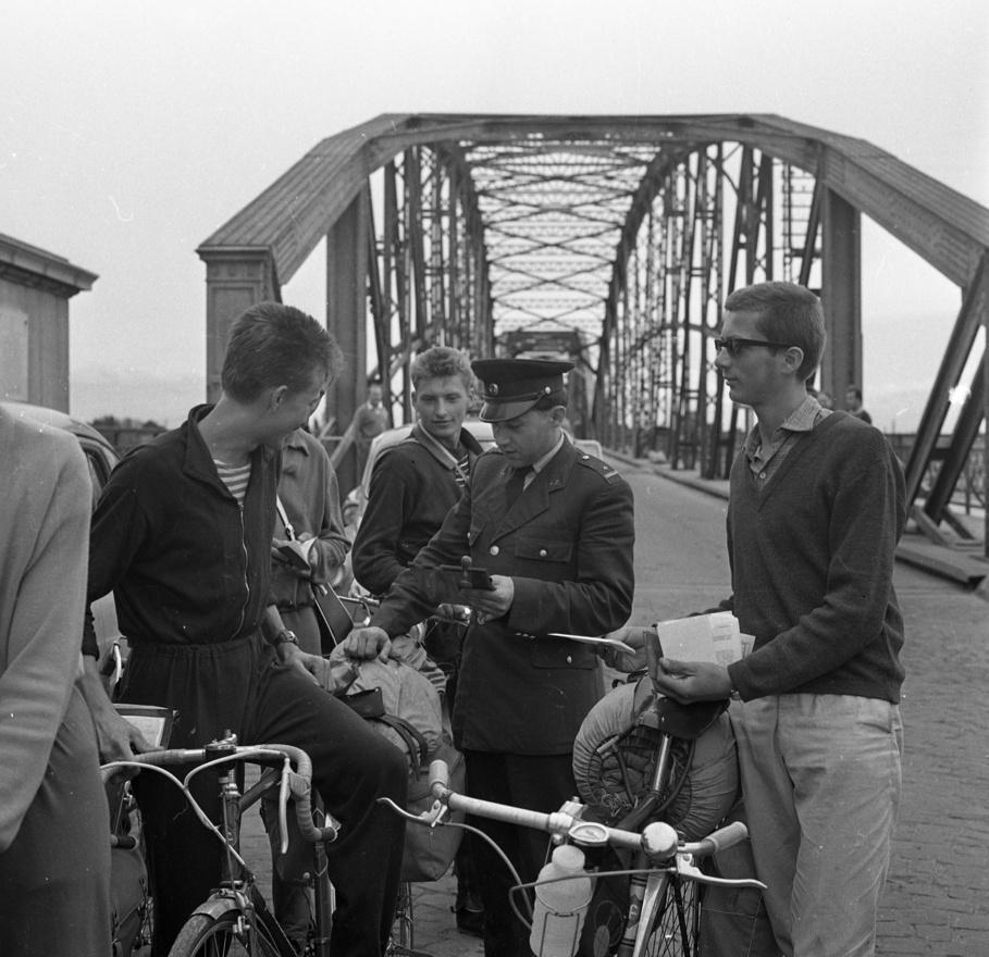 """1964-ben a komáromi csehszlovák-magyar határon halad át biciklivel három korabeli hipszter. Valuch Tibor a Hétköznapi élet Kádár János korában című könyvében azt írja, hogy az öltözködésben nagyjából ekkoriban lett látható a különböző ifjúsági szubkultúrák, a beat- és rocknemzedék elkülönülése a kor idősebb generációitól. A hatvanas évek legelejétől kezdett fellazulni az negyvenes-ötvenes években ismert, a központi vezetés szándékaként az öltözködésben is megnyilvánuló kényszerpuritán, uniformizált divat, a komáromi határálépők között jobboldalt, napszemüvegben álló menő fiatalember ennek a jelenségnek méltó hordozója. """"A legfiatalabb generációk tagjainak jellemző öltözete lett a hatvanas évek végére a bő szárú pantalló, a mintás ing és a színes, műszálból készített pulóver"""" - írja Valuch a könyvében."""