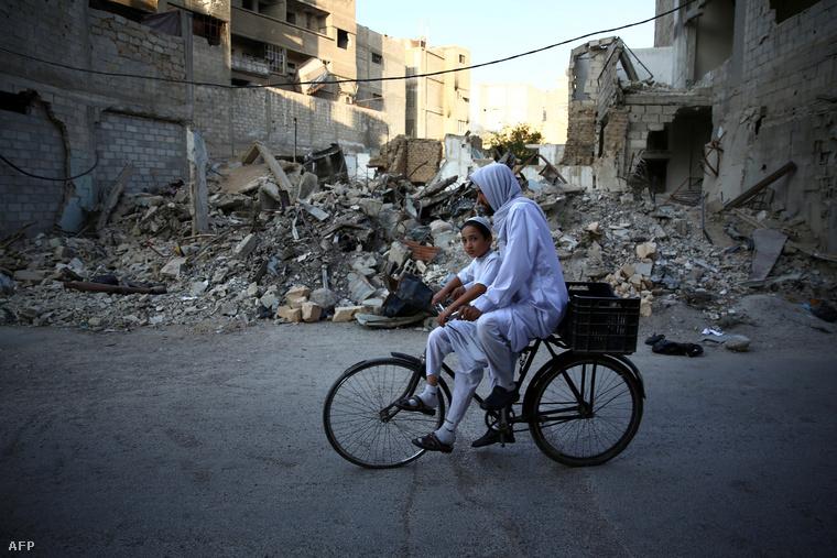 Damaszkusz romjai között bicikliző szír apa a gyerekével.