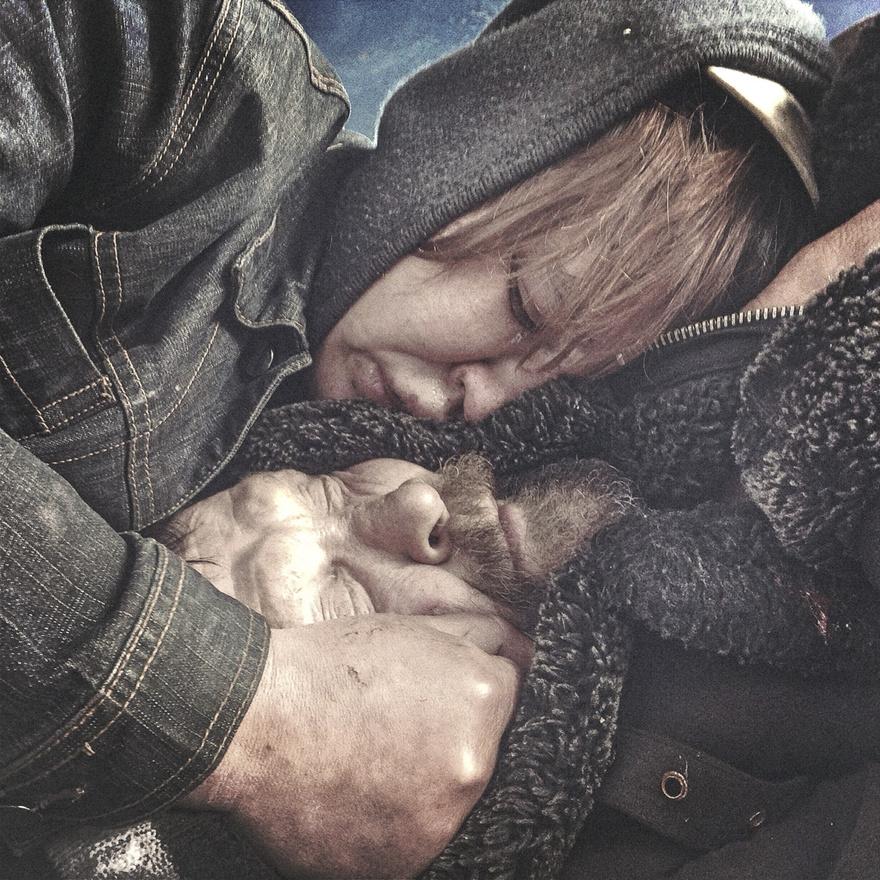 Két hajléktalan próbálja egymást melegen tartani az őszi hidegben egy pszkovi parkban.