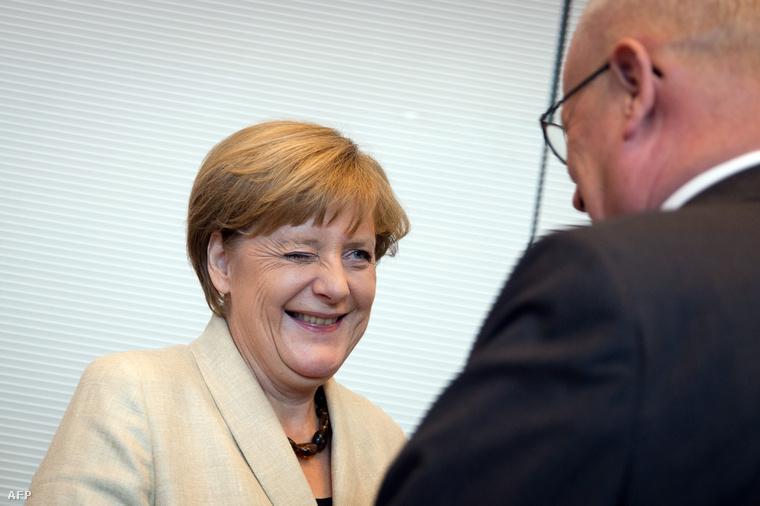 Angela Merkel kacsint rá a CDU képviselőcsoport vezetőjére, Volker Kauderra egy frakcióülés előtt Berlinben, 2015. szeptember 29-én.