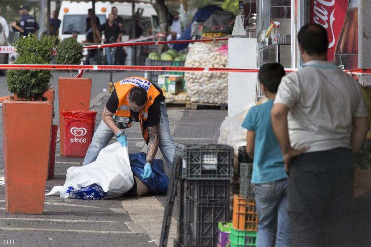 Egy izraeli orvos vizsgálja a palesztin támadó holttestét akit izraeli rendőrök lelőttek miután két ultraortodox zsidót késsel könnyebben megsebesített a Damaszkuszi kapu közelében Jeruzsálemben 2015. október 10-én.