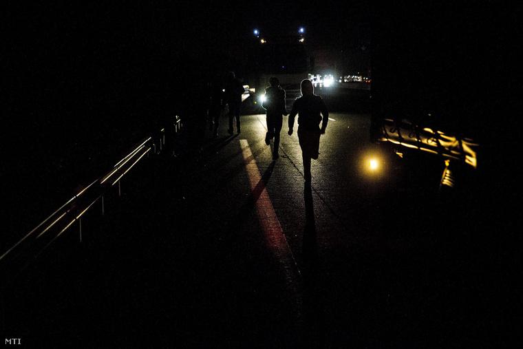 Nagy-Bitanniába igyekvő bevándorlók próbálnak felugrani egy teherautóra a Londont Párizzsal és Brüsszellel a La Manche csatorna alatt összekötő Csatorna-alagút fraqnciaországi bejáratánál Calais-ben 2015. június 25-én.