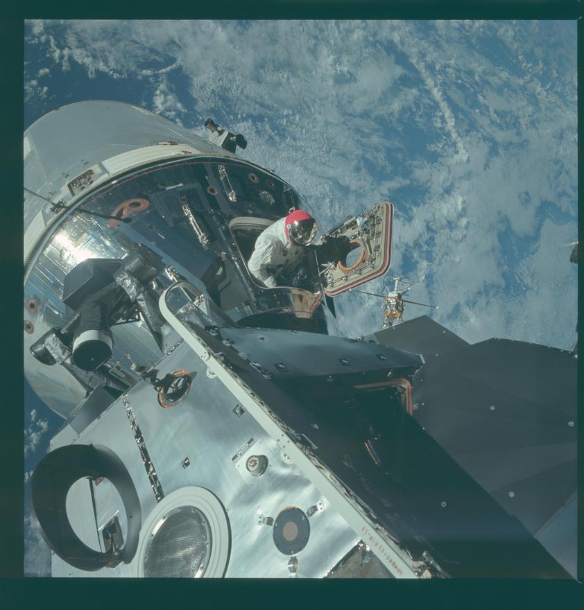 Dave Scott mászik ki az űrhajóból a 9-es Apollo-küldetéskor. Scott az anyahajó parancsnoka volt, és amit látunk, az az űrséta egyszerűsített formája, amikor az űrhajós nem hagyja el a zsilipet, csak kiemelkedik rajta, például hogy fényképezzen. A kép további érdekessége a piros sisak: az Apollo-9 nem ment el a Holdig, ezért nem a közismert fehér sisakot használták, már csak azért sem, mert azt épp ekkoriban fejlesztették. Ez a piros sisak átmenet volt a félig fém, félig üveg sisakok, és az átlátszó üvegbuborék sisakok között.