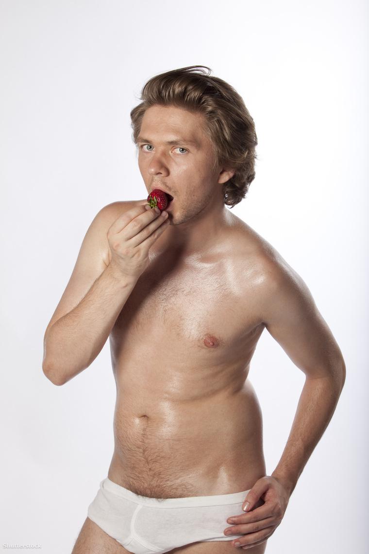 Csábító Fiatalember csábítóan epret eszik