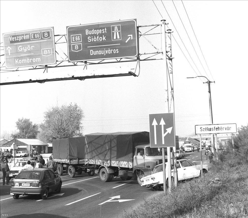 A benzináremelés ellen tiltakozó taxisok és fuvarosok útzárja a Székesfehérvárra vezető főútnál 1990. október 26-án. Délre az egész ország közlekedése összeomlott. Csak az élelmesek jutottak át a blokádon: volt, aki a füvön kerülte meg az útzárt, volt, aki inkább traktorra váltott és földutakon közlekedett.                          A kormány napközben sem tudott megegyezni a taxisokkal, a Népjóléti Minisztérium kérésére a                         demonstrációban résztvevők a mentőautókat, a rendőröket és a kivonuló orosz csapatokat engedték át az útzárakon. Időről időre a civilek egy része előtt is megnyitották az úttorlaszokat.