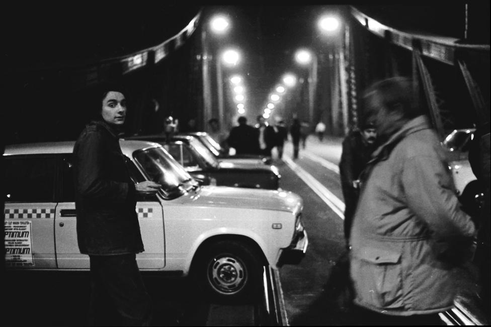 Tüntetők a lezárt Szabadság híd pesti hídfőjénél. A felháborodott taxisok és fuvarozók szervezni kezdték a hidak lezárását. CB-rádión értesítették egymást az akcióról. Budapesten ekkor 19-20 ezer engedélyes taxis volt – 1990-ben a nyolcmilliós New Yorkban csak 18 ezren taxiztak. Este tízre elvágták egymástól a budai és a pesti oldalt. Nemcsak Budapesten, Komáromtól Dunaföldvárig blokád alá vették a Duna-hidakat.