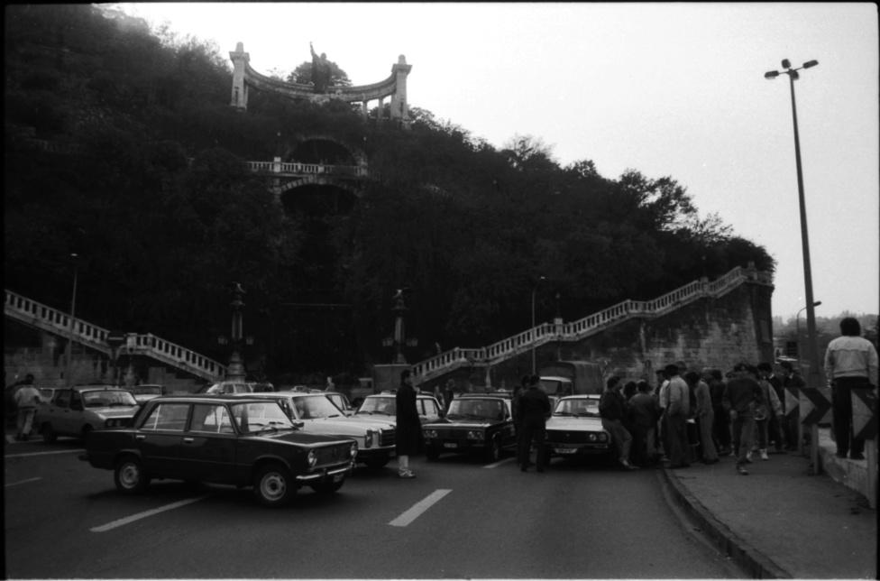 """Blokád az Erzsébet-híd budai hídfőjénél. A taxisok rendőri felvezetéssel átvonultak a Felvonulási térről a Kossuth térre. Éjfélig adtak haladékot a kormánynak, hogy visszavonja a döntést. Az esti bejelentést egyetlen kormánytag nem vállalta magára, helyettük egy szóvivő: Kardos Antalné közölte a 65 százalékos áremelést. A Parlament lépcsőjén Siklós Csaba közlekedési, hírközlési és vízügyi miniszter tárgyalt a taxisokkal. """"A kormány kényszerhelyzetben van, nincs mód a visszavonásra"""" – közölte a tüntetőkkel."""