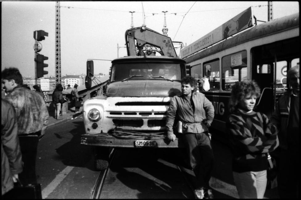 Teherfuvarozó állja el a villamos útját a budapesti Szabadság-hídon. 1990. október 25-én, csütörtök este az öt hónapja hivatalban lévő Antall-kormány bejelentette: 65 százalékkal, típustól függően 42-62 forinttal emeli az üzemanyagárakat. A meglepő döntést a szovjet kőolaj- és földgázszállítmányok csökkentésével és Kuvait iraki lerohanásával indokolták.