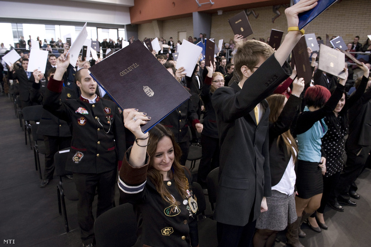 Végzős hallgatók emelik magasba okmányaikat a Dunaújvárosi Főiskola diplomaosztó ünnepségén 2013. február 9-én.