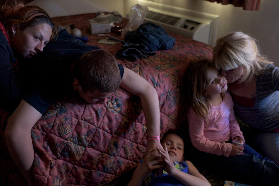 """Vinny 16 éves ezen a fotón, és éppen kisöccsét, Michaelt csikizi. Vinny barátnője Krystle látható még a képen, mindannyian egy motelben vannak, ahol a kisebb testvérek az apukájukkal élnek. """"Boldog vagyok, ha az anyukámmal, a kistestvéreimmel és a bátyámmal lehetek"""" – mondja Vinny."""