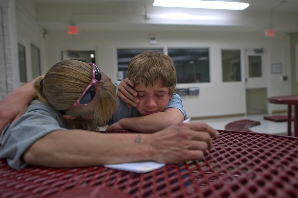 """""""Amikor anyukámat verte, nagyon féltem, és meg akartam védeni őt. Elegem lett abból, hogy azt látom, bántják az anyukámat"""" – mondta Vinny a fotósnak. A képen Eve-vel, édesanyjával a börtönben ölelkeznek egy találkozón."""