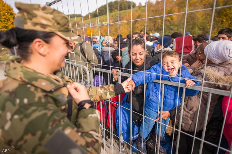 Egy szlovén katona játszik egy menekült kisfiúval a szlovén-osztrák határnál, 2015. október 25-én.