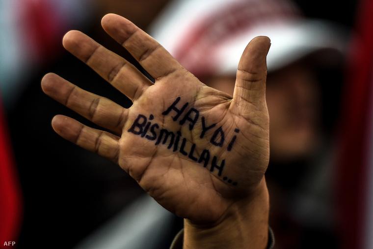 """""""Tovább, Allah nevében"""" áll egy AKP szimpatizáns kezén, a 2015. október 25-ei felvonuláson."""