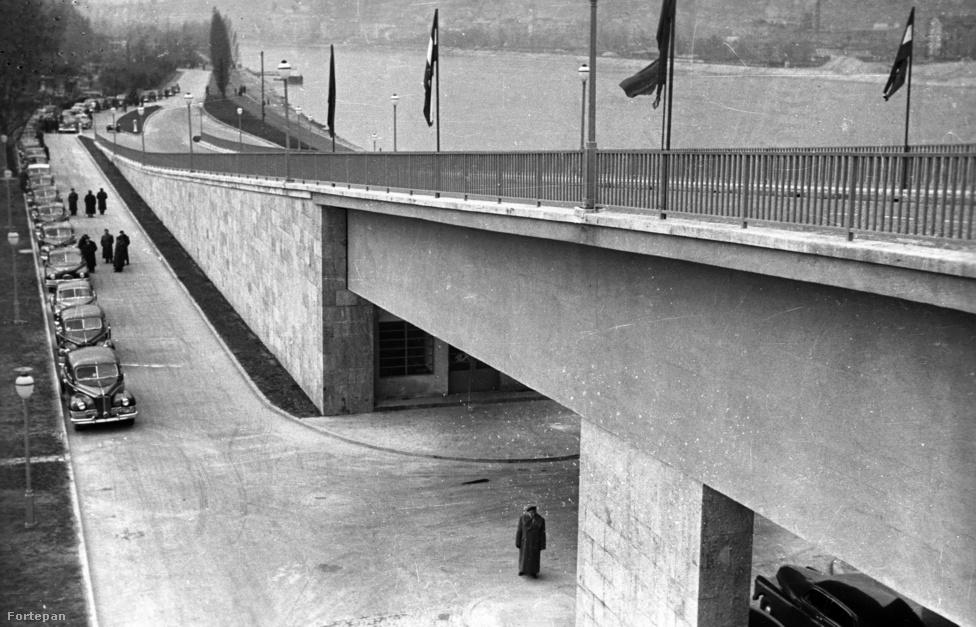 A zászlók nélkül is kitalálhatnánk, hogy ünnepség van: ennyi autó egy helyen ritkán jött össze Budapesten 1950-ben. A híd szigeti lehajtója kifejezetten modernnek hat, akár ma is megállná a helyét ez a dizájn, mely nagyrészt 30-as évekbeli terveket követ.