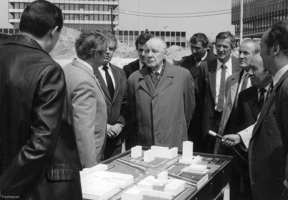 Pár lépéssel és két évtizeddel odébb Kádár János kér tájékoztatást az Árpád hídi közlekedési rendszer építéséről, mindenféle tanácsi és állami tótumfaktumoktól. Mögötte a mai Nyugdíjfolyósító és a MÁK épülete, melyek előtte is láthatók: a makett jobb sarkában. Tulajdonképp ugyanez a felállás ma is, mint a terven, csak egy Rendőrpalotával meg egy buszpályaudvarral egészült ki a kép.