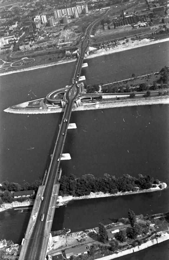 Ezen az 1963-as légi felvételen gyönyörűen látszik milyen széles lett volna a híd (a kép alján a Hajógyári-sziget két nyúlványán), és milyen lett, amikor megépült. A pesti oldal még egészen más képet mutat mint ma, igaz néhány lakótelepi ház már áll, bár megvan még a korábbi képekről ismerős kémény is.