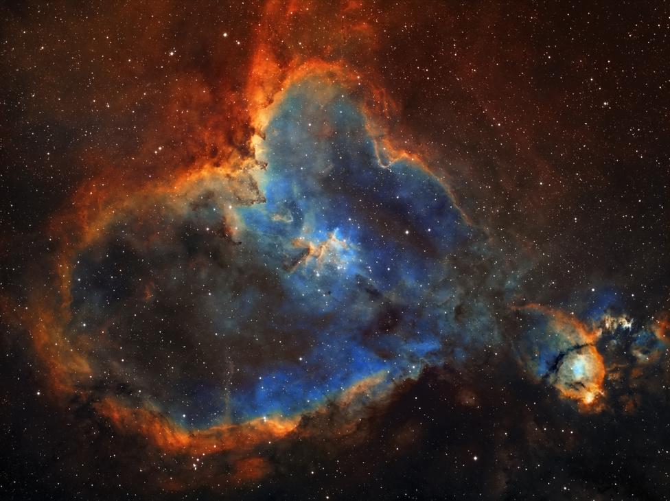 Szív-köd (Kompozíció, forma és kísérletezés kategória)A köd otthonául szolgáló Cassiopeia a jellegzetes W alakja miatt jól ismert égi alakzat, még a csillagászatot közelebbről nem ismerők előtt is. Az északi félgömb egyik legnépszerűbb cirkumpoláris csillagképe számos gyönyörű mélységobjektumot rejt, ám ezek közül is kiemelkedik a rendkívül jellegzetes alakú, szív formájú ködösség. Az IC 1805 megközelítőleg 7500 fényévre található a Napunktól, a Perseus-karban helyezkedik el. A Szív-köd közepét a laza szerkezetű Melotte 15 halmaz uralja. A szív csúcsában található igen fényes csomó külön katalógusszámot visel: NGC 896-ként ismerjük, fényessége miatt jóval korábban felfedezték, mint a teljes alakzatot.