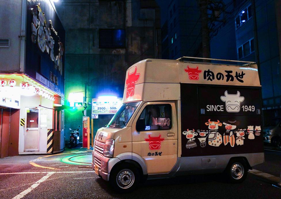 Esti csendélet dupla magas kei-furgonnal és kandzsikkal. A háttérben egy autóforgató – minden parkolóház előtt van ilyen, hogy a kihajtani készülőnek ne tolatnia kelljen a forgalomba, hanem orral előre indulhasson el. Nálunk, Budapesten az a szenzáció, hogy már van ilyen, Japánban, 1977-ben már teljesen általános volt. Most már a kis utcák is tele vannak velük
