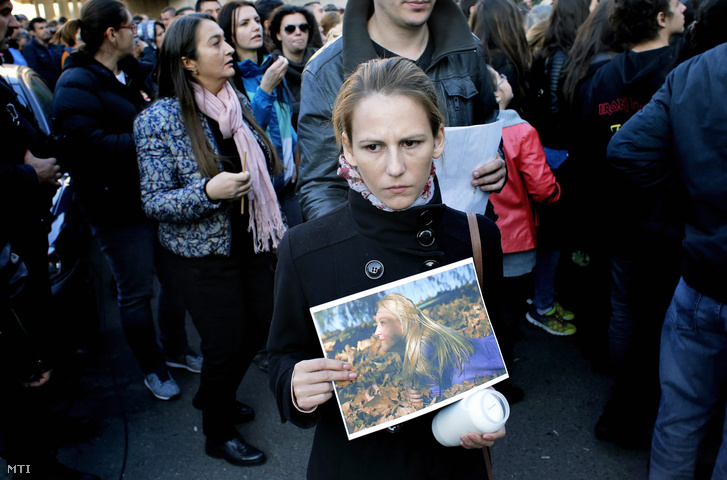 A diszkótűz áldozatul esett barátnője képét fogja egy nő Bukarestben 2015. november 1-jén.