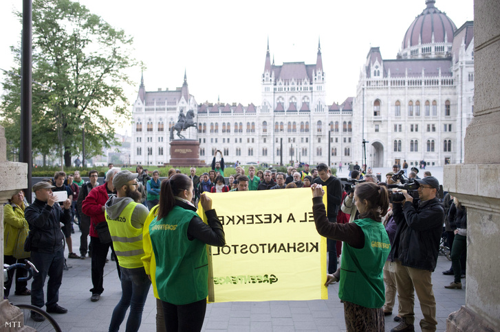 Greenpeace-aktivisták EL A KEZEKKEL KISHANTOSTÓL! feliratú transzparenst tartanak a Vidékfejlesztési Minisztérium előtt a Kettős Mérce blog demonstrációján 2014. április 12-én.