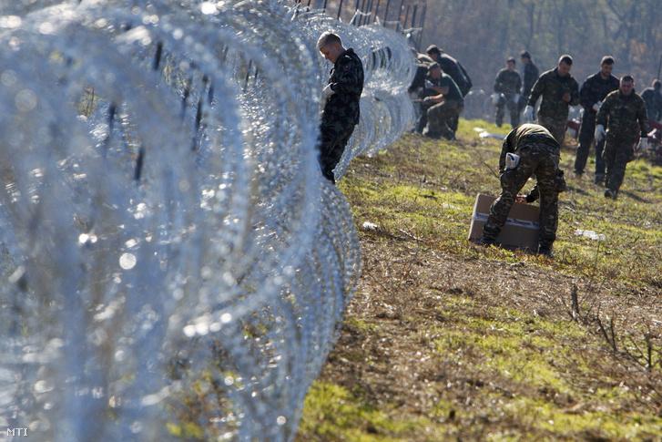 Szlovén katonák pengésdrótból építenek kerítést a szlovén-horvát határon Gibinánál (Murafüred)