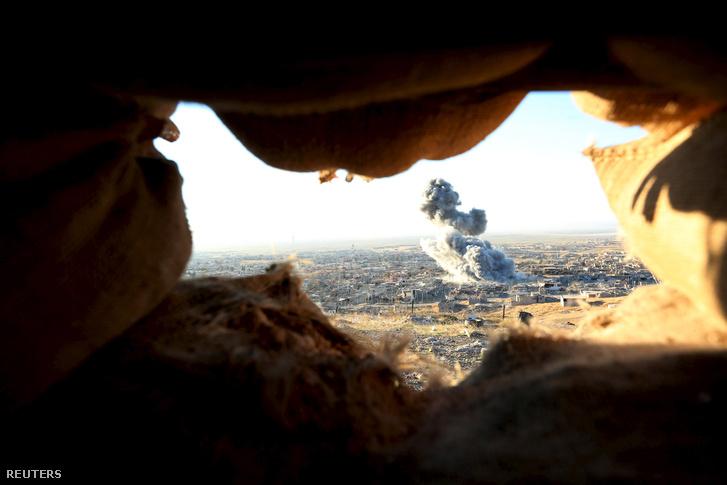 Füst száll fel egy épületből a bombázás után Szindzsárban november 12-én