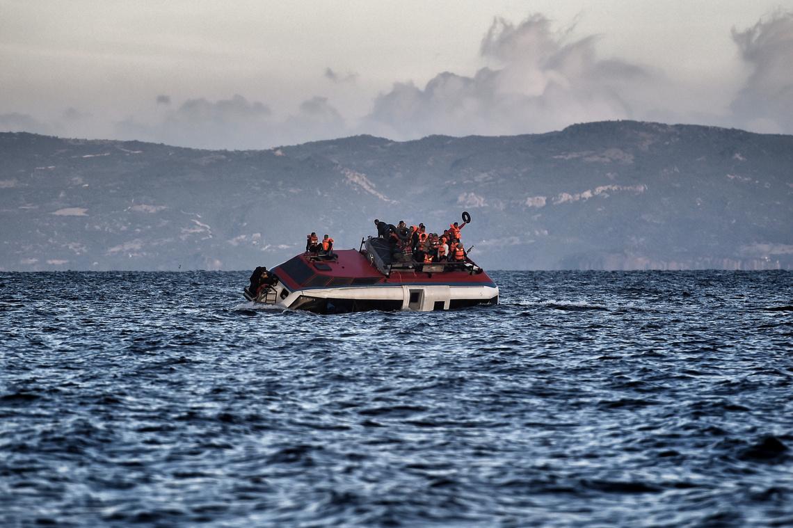 Leszbosz mellett süllyed egy hajó, a menekültek a tetőre zsúfolódva várják a segítséget.