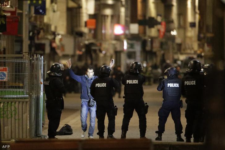 Egy járókelőt igazoltatnak a rendőrök az akció helyszíne közelében Saint Denis-ben