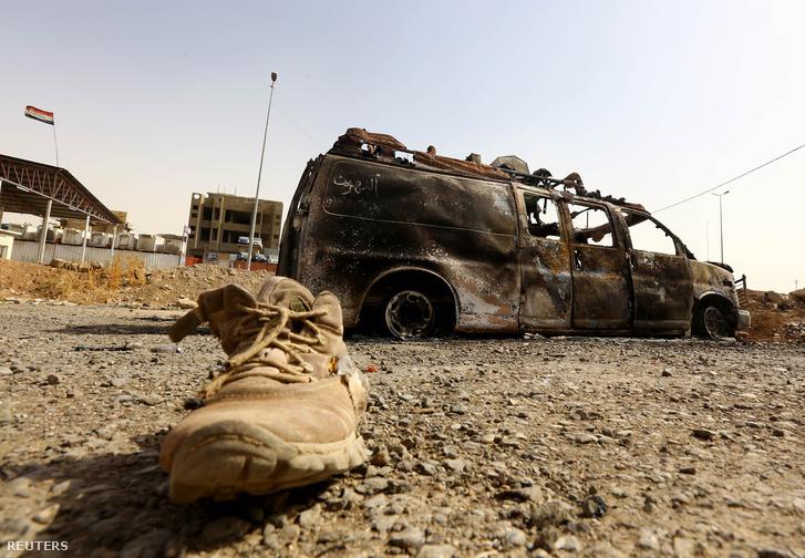Moszul és egy kiégett iraki katonai autó, 2014. június 11-én.