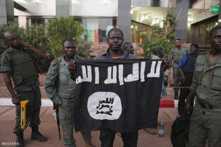 A helyi biztonsági szolgálat tagjai mutatnak egy ISIS zászlót, amelyet a hotelt megtámadó fegyveresekhez kötnek.