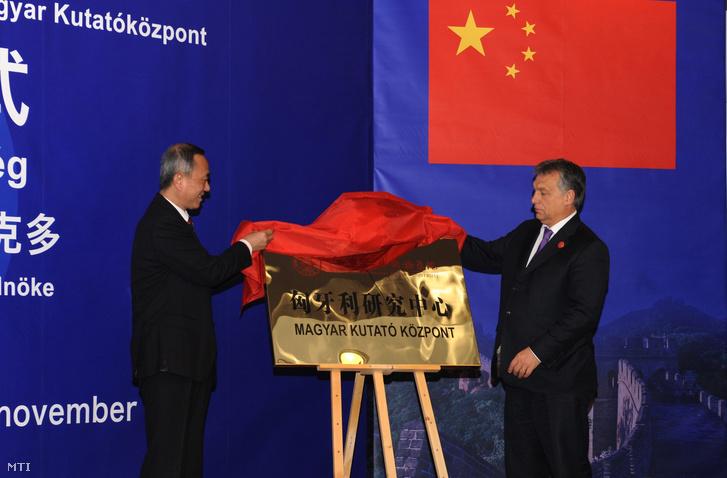Orbán Viktor miniszterelnök (j) és Feng Pej az egyetemi tanács elnöke a Magyar Kutatóközpont táblaavatási ünnepségén a Pekingi Nemzetközi Tanulmányok Egyetemén.