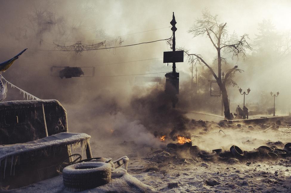 Hrusevszkij utca Molotov-koktélok füstjében. Az utca – ahol a Dinamo Kijev stadionja is áll – a Majdan mellett a tiltakozások egyik központja volt, hiszen itt van három minisztérium és a kormány épülete is. A főtér után a legtöbb áldozat ezen az utcán halt meg. Janukovics elnök ekkor még úgy érzi, megmaradhat posztján, legalább mandátuma 2014 végén esedékes lejártáig.