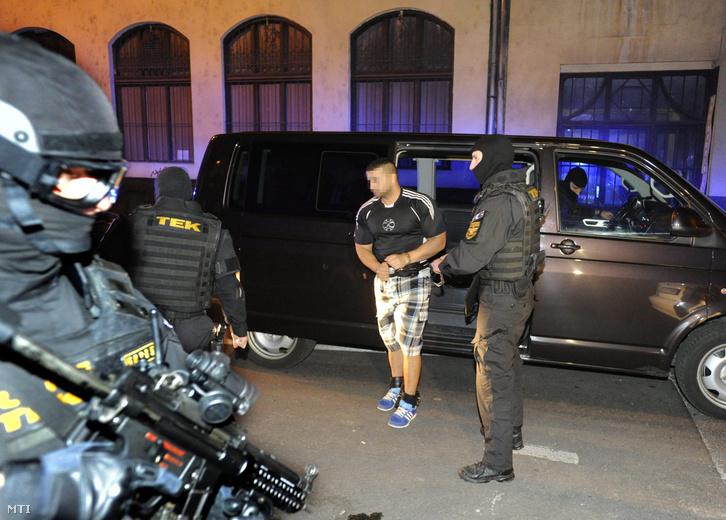 A TEK munkatársai kéz- és lábbilincsben vezetik a házi őrizetből megszökött majd Svájcban elfogott ároktői banda két tagjának egyikét, a 26 éves R. Henriket a Nemzeti Nyomozóiroda épületébe 2013. október 21-én este.