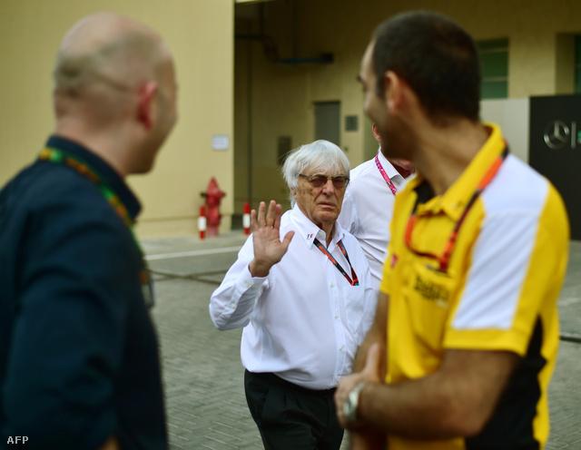 Ecclestone a Renault menedzser igazgatójának, Cyril Abiteboulnak (sárgában) int Abu-Dhabiban