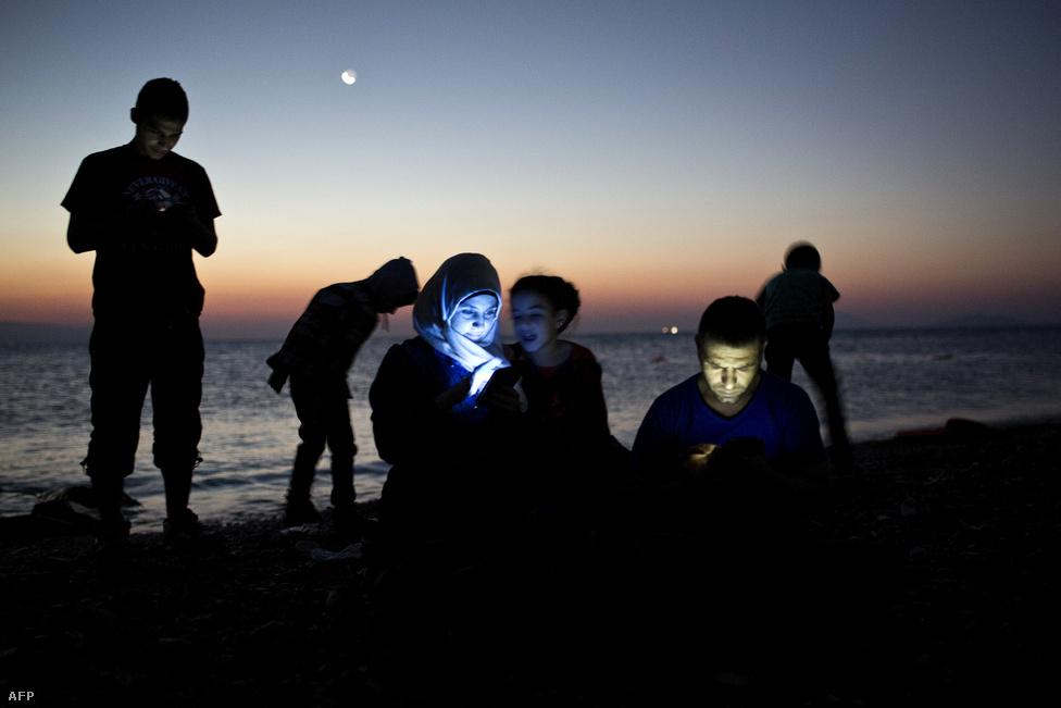 Partot ért menekültek telefonálnak haza Koszról, augusztus 12-én.