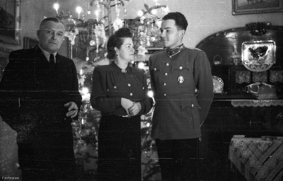 """Valószínűleg otthon karácsonyozik 1940-ben egy fiatal katona. Karácsony előtt két héttel írtuk alá a magyar-jugoszláv örök barátsági egyezményt, majd pár hónappal később megszegtük. Teleki Pál öngyilkos lett emiatt, """"a gazemberek oldalára álltunk"""" – írta búcsúlevelében. Ha sejtették is a kép szereplői, hogy hamarosan milyen drámaian negatív fordulatot vesz az ország sorsa, akkor se látszik rajtuk."""