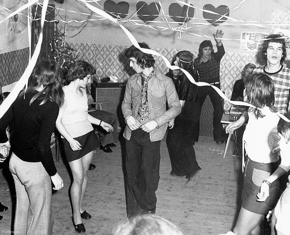 Szintén 1973, de itt inkább egy művelődési házban mehet a buli. Illetve még csak kezd beindulni, mert a szégyenlős fiúk még csak a terem szélén üldögélnék. A hangfalaknál beterpesztő fickónak van igaza, ezek a trapéznadrágok és magas sarkú cipők csak úgy nem fogják megtáncoltatni magukat. 1973 legnagyobb slágerei közt olyanok voltak például a világban, mint a Smoke on the Water vagy a Killing Me Softly. Itt nem tudjuk, mire ropják, de ha újabb magyar számokat hallgattak, akkor mehetett már a Taurustól a Zöld csillag, vagy mondjuk az LGT-től a Gyere, gyere ki a hegyoldalba. Vagy épp Szécsi Páltól a frissen átvett Carolina.