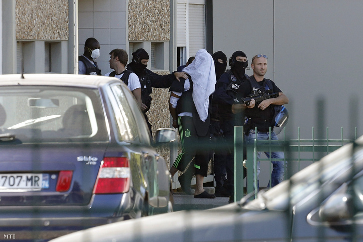 A törölközővel letakart arcú Yassin Salhit kísérik ki rendőrök az otthonából a Lyon környékén fekvő Saint-Priestben 2015. június 28-án.