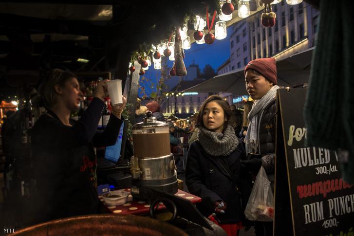 Külföldi turisták Budapesten a Vörösmarty téri karácsonyi vásárban 2015. december 25-én.