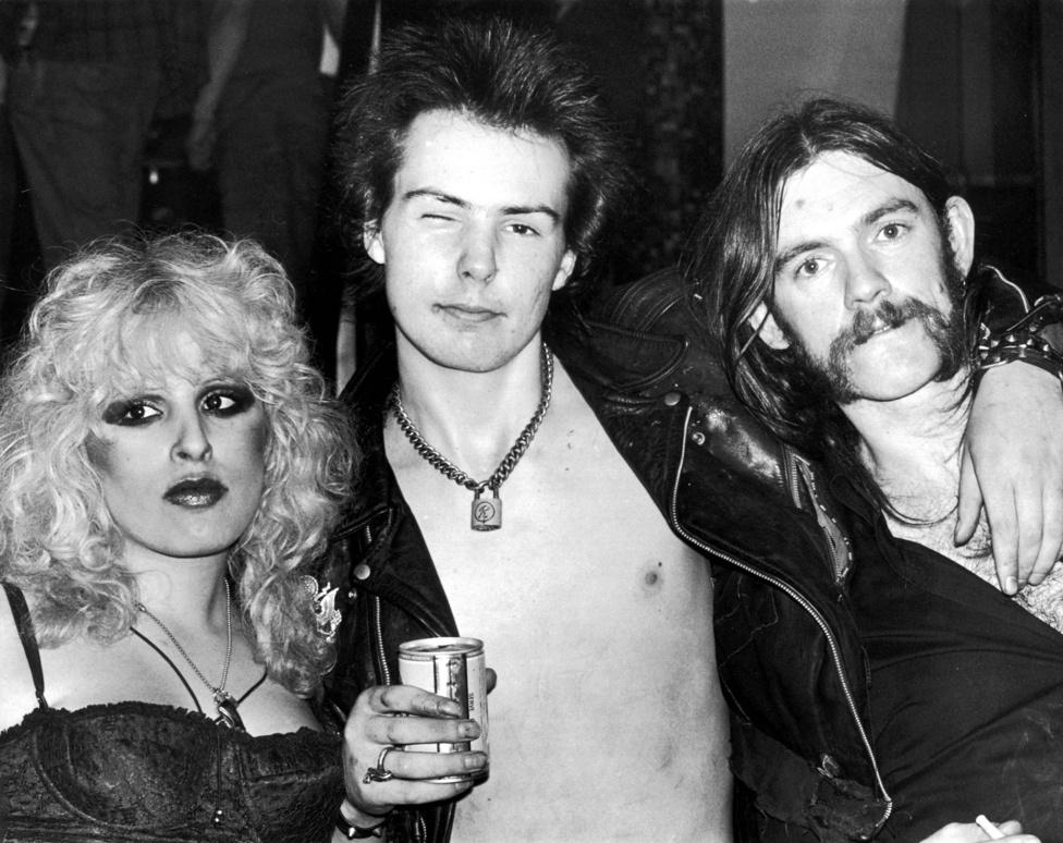 Lemmy Kilmister 1945 december 24-én született a brit Stoke-on-Trent városában. Egész fiatalon bekerült az Egyesült Királyság pezsgő zenei életébe, ami egy Beatles koncerttel kezdődött és azzal folytatódott, hogy Lemmy Jimi Hendrix technikusa lett. Ezen a korai képen a zenetörténet Bonnie és Clyde párosának megfelelő Sid Vicious és barátnője Nancy látható Lemmy mellett.